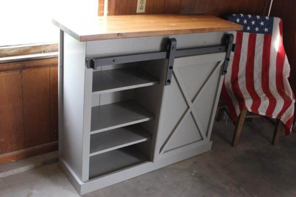 Gray sliding barn door console table with brown stained top and adjustable shelves with an American flag