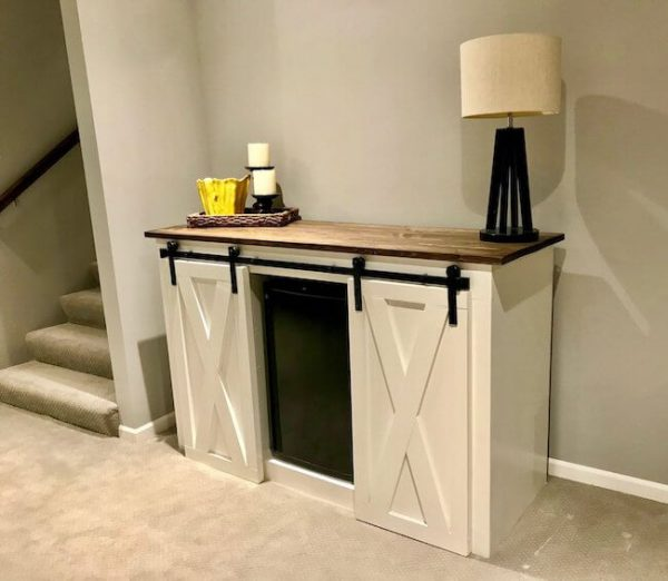 Double door sliding barn door media console with mini fridge in the middle and lamps and candles on top of it, white with brown stained dark walnut top