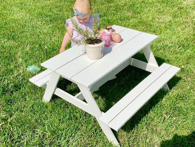 Girl with bow outside playing on a kids picnic table custom made with green grass and her baby doll and a flower pot