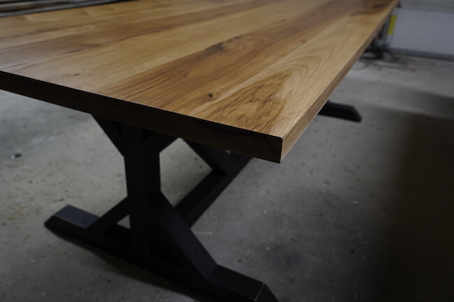 detailed shot of a hickory pedestal trestle dining table