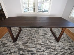 walnut live edge dining table with walnut pedestal base on modern style rug