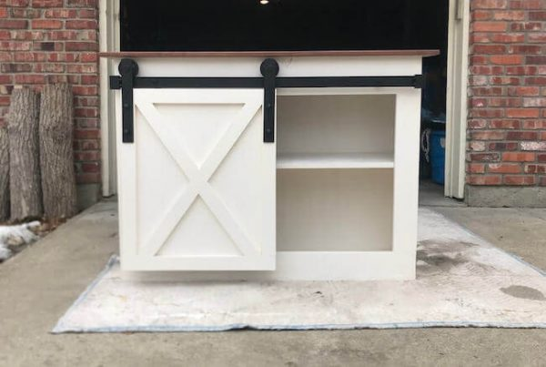 Sliding barn door media console with X on door, walnut top and adjustable shelf, painted white base