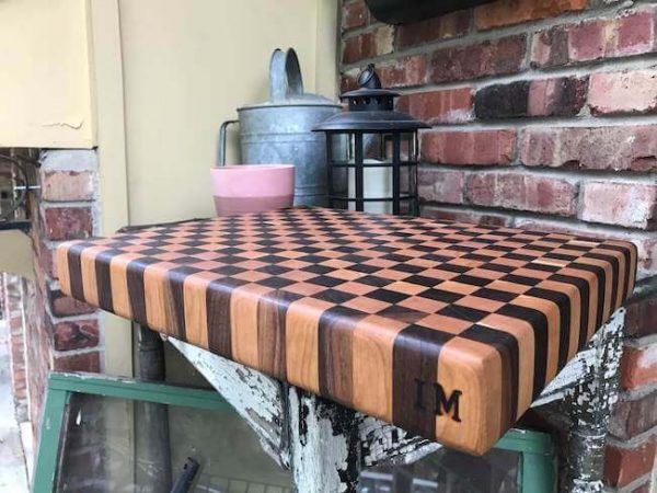 Walnut and cherry end grain cutting board with customized lettering on the edge