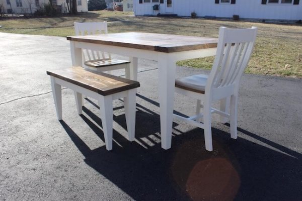 Tapered leg dining table and bench with matching chairs in a painted pure white with dark walnut stain