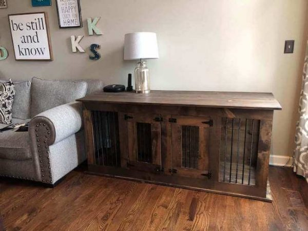 Brown dog kennel custom made with double doors and lamp on top of it next to a gray couch