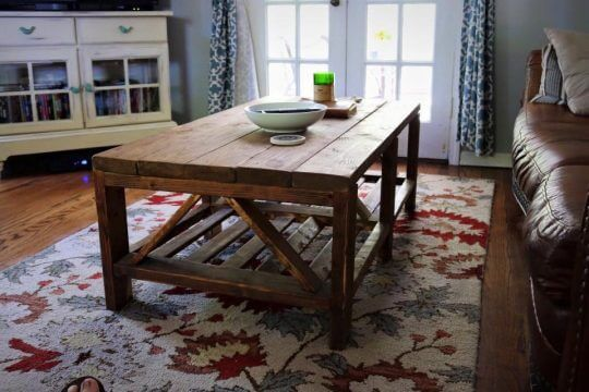 Rustic triple truss coffee table in dark walnut, distressed in a farmhouse style furniture look, white bowl and green candle