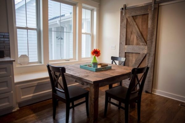 Farmhouse style custom made dining table and dining chairs in a rustic farmhouse setting with reclaimed wood sliding barn door stained dark walnut