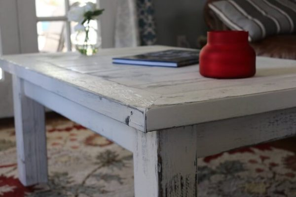 custom made distressed white coffee table with candle and book on top