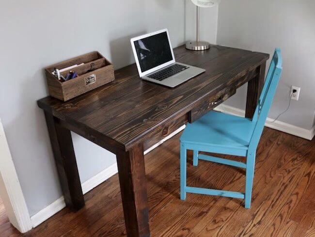 Farmhouse style home office desk with light blue accent chair and laptop computer