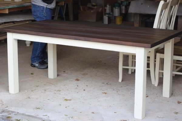 Walnut dining table with straight legs that are painted white