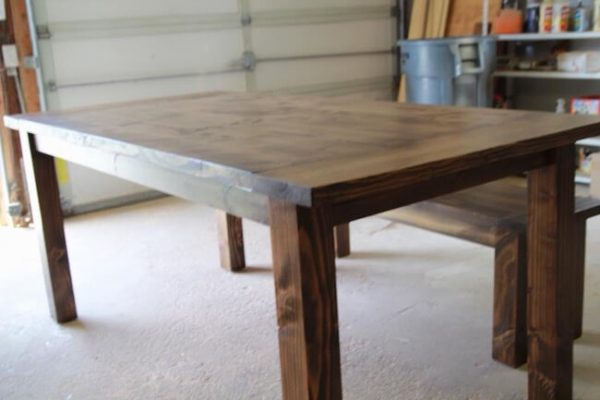 Custom made turned leg farmhouse dining table stained in dark walnut with a smooth rustic top