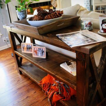 Rustic X console table in a french country home setting with two shelves and various decorations