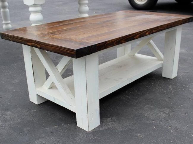 Chunky legged coffee table with X design, painted antique white base with a dark walnut top