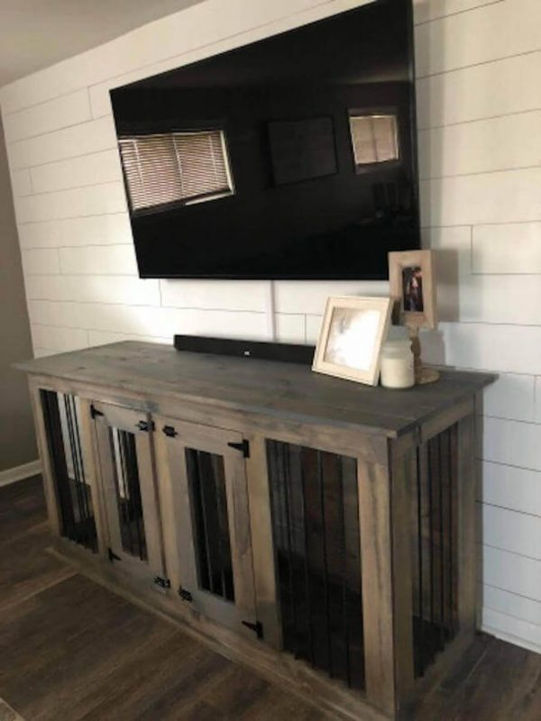 Double door dog kennel in a weathered gray stain with a TV above it and white shiplap walls