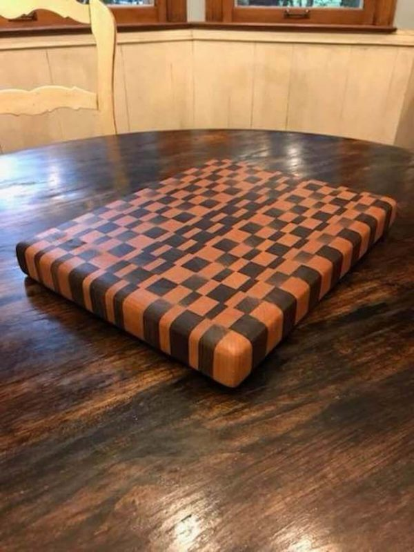 Walnut and cherry end grain cutting board on a round dining table