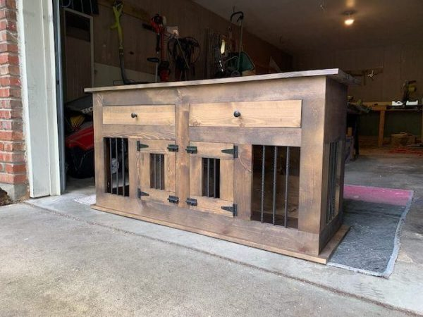 Two doors on a dog kennel with shelves and black hardware stained dark walnut