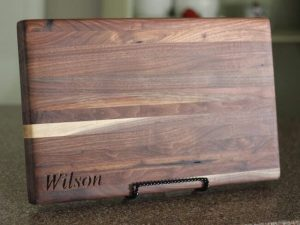 Rectangular brown walnut edge grain cutting board with customized last name in corner