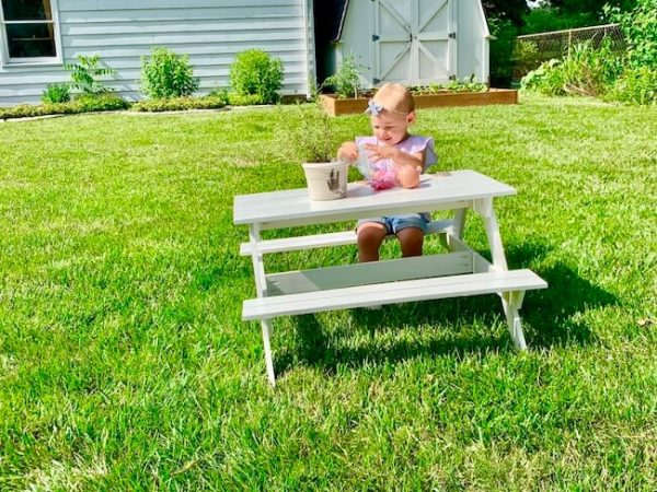 Girl playing with her doll on custom made picnic table outside in the summer