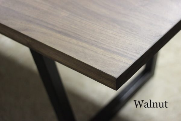 Detailed shot of a modern walnut dining table and steel tube legs