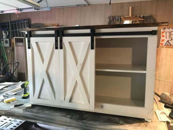 Double sliding barn door media console with X's on doors and black hardware, painted white base and dark walnut stained top