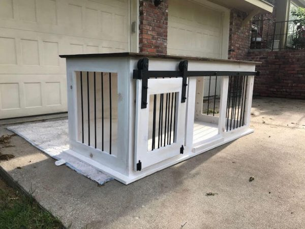 Sliding barn door dog kennel with distressed white paint and dark walnut stain top